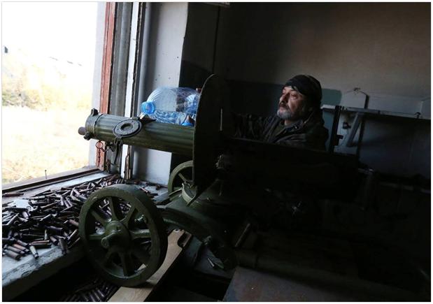 Ukraiński ochotnik uzupełnia wodę do chłodzenia karabinu Maxim wz. 1910, miejscowość Piaski, rok 2014. (Źródło: https://www.facebook.com/UIKNPW/posts/2177516452509480)